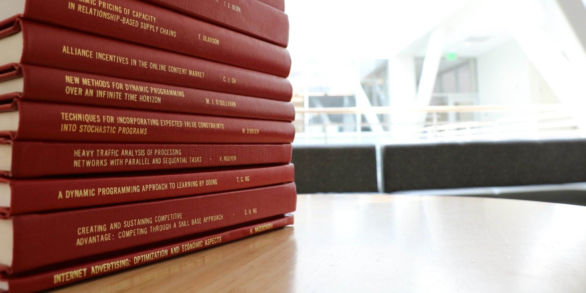 a stack of PhD theses bound in cardinal reddish covers on a table in the Huang Engineering Center