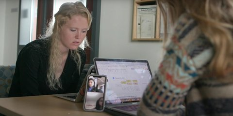 Two female students working on their laptops together at a table while on a phone call with another student